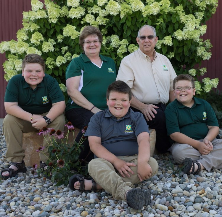 Greentown Flooring Family sitting down posing for a company photo.