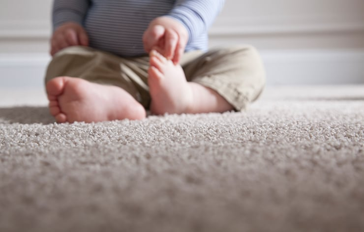 Baby sitting on carpet.